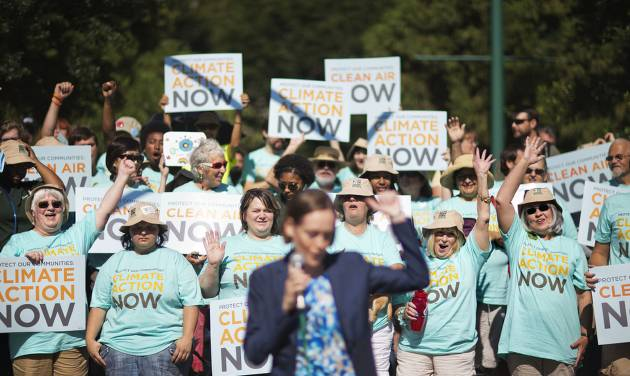 Clean air advocates cheer as Mary Anne Hitt, director of the Sierra Club's Beyond Coal Campaign, speaks at a rally outside an Environmental Protection Agency hearing, Tuesday, July 29, 2014, in Atlanta. Utility and coal companies are expected to argue Tuesday against proposals from the Obama administration that would force a 30 percent cut in carbon dioxide emissions by the year 2030 from 2005 levels. The EPA is holding three public hearings on the proposal in Atlanta, Denver and Washington. (AP Photo/David Goldman)