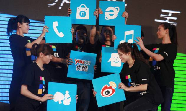 In this March 28, 2012 photo, Chinese performers hold up cards showing the various apps available for online users for shopping and other services at the launch of a mobile phone in Beijing, China. In an abrupt shift, some 81 percent of China's 618 million Internet users go online via smartphone or tablet, part of a worldwide trend known as the mobile Internet. The services Chinese users flock to are usually privately owned, while the competitors they leave behind belong to the state. Video websites compete with state TV, online financial services draw deposits away from banks and instant messaging apps take revenue from government-owned phone carriers. (AP Photo/Ng Han Guan)