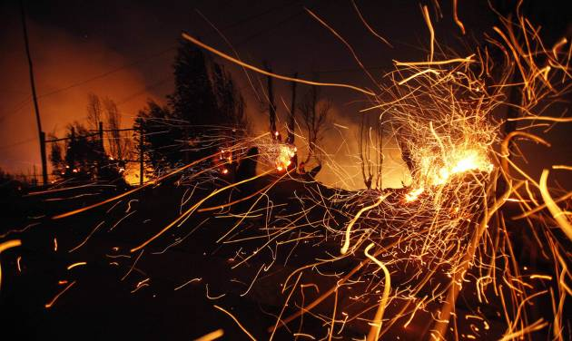Sparks fly carried by the wind as a large forest fire reaches urban areas in Valparaiso, Chile, Sunday April 13, 2014. Authorities say the fires have destroyed hundreds of homes, forced the evacuation of thousands and claimed the lives of at least seven people.  ( AP Photo/ Luis Hidalgo)