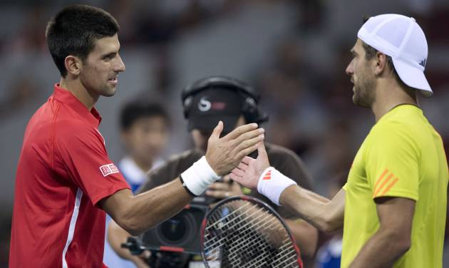 Serbia's Novak Djokovic, left, shakes hands with Jurgen Melzer of Austria after their men's singles quarterfinal match of the China Open tennis tournament in Beijing Friday, Oct. 5, 2012. Djokovic defeated Melzer 6-1, 6-2. (AP Photo/Andy Wong)