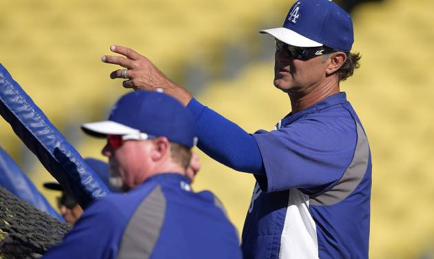 Los Angeles Dodgers manager Don Mattingly, right, talks with batting coach Mark McGwire during batting practice prior a baseball game against the Atlanta Braves, Thursday, July 31, 2014, in Los Angeles. (AP Photo/Mark J. Terrill)