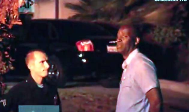"""In this image taken from video from OnScene.tv, actor Michael Jace, right, is detained by police outside his home in Los Angeles on Monday night, May 19, 2014. Jace, who played a police officer on the hit TV show """"The Shield,"""" was arrested on suspicion of homicide after his wife was found shot to death in their Los Angeles home, authorities said. (AP Photo/OnScene.tv)"""