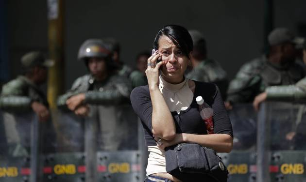 An inmate's relative cries as she uses a cell phone outside La Planta prison where National Guard soldiers stand behind in Caracas, Venezuela, Saturday, April 28, 2012. Hundreds of inmate's relatives were not allowed to enter for normal visiting hours because they were canceled after authorities foiled plans for a prison break on Friday. Venezuelan authorities say they discovered a tunnel that inmates had dug leading to a sewer. (AP Photo/Ariana Cubillos)
