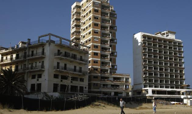 A couple walk on the beach by the deserted hotels in an area used by the Turkish military in the Turkish occupied area in the abandoned coastal city of Varosha, in Famagusta, in southeast of island of Cyprus, Friday, Jan. 17, 2014. Time virtually stopped in 1974 for the Mediterranean tourist playground of Varosha. When Turkey invaded Cyprus in the wake of a coup by supporters of union with Greece, thousands of residents fled, and chain-link fences enclosed a glamorous resort that it's said once played host to Hollywood royalty like Elizabeth Taylor. The town's crumbling, war-scarred beachfront hotels have become an emblem of the country's division between Turks and Greeks. In 40 years, few have set foot inside the town, which remains heavily guarded by the Turkish army and twists of barbed wire. But that grim scene could present a rare opportunity. Massachusetts Institute of Technology architecture professor Jan Wampler calls it the greatest challenge of his career: he and a team of architects, urban planners, business leaders and peace activists hope to rebuild an entire town to correct past errors and mold a sustainable, ecological habitat. (AP Photo/Petros Karadjias)