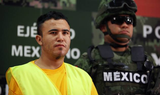 "An Army soldier stands next to Daniel Ramirez, alias ""El Loco,"" during his presentation to the media in Mexico City, Monday, May 21, 2012. Ramirez is believed to be a member of the Zetas drug cartel allegedly involved in the dumping of more than 40 hacked-up bodies on a highway outside the city of Cadereyta near Monterrey. The bodies with their heads, hands and feet hacked off were found May 13. (AP Photo/Alexandre Meneghini)"