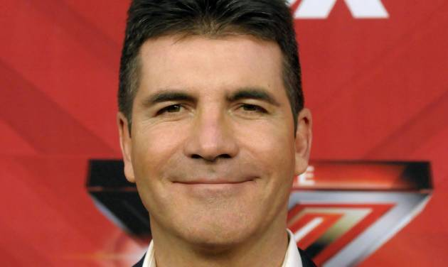 "FILE - In this Dec. 22, 2011, file photo, television personality Simon Cowell poses on the red carpet at The X Factor Finale show in Los Angeles.  Simon Cowell said Monday, Dec. 16, 2013, he is plotting changes for ""The X Factor,"" including new judges and a new role for him.(AP Photo/Dan Steinberg)"