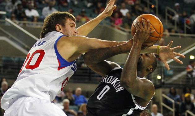 Brooklyn Nets' Andray Blatche (0) is fouled by Philadelphia 76ers' Spencer Hawes (00) during the second half of an NBA preseason basketball game in Atlantic City, N.J., Saturday, Oct. 13, 2012. The Nets defeated the 76ers 108-105 in overtime. (AP Photo/Rich Schultz)