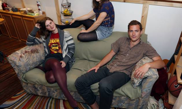 Lara Russo, left, Cally Guasti, center, and Reese Werkhoven sit on a couch in their apartment in New Paltz, N.Y. on Thursday, May 15, 2014. The roommates had purchased it at a Salvation Army store and found $40,800 stashed inside. After finding a deposit slip, they returned the money to the 91-year-old upstate New York widow who had hidden it there. (AP Photo/Mike Groll)