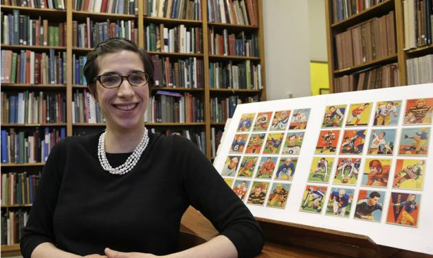 Assistant curator Freyda Spira, of the department of drawings and prints, poses with football cards, Wednesday, Jan. 8, 2014, part of an exhibition to be mounted at the Metropolitan Museum of Art in New York. The museum better known for high art, is presenting a pop-up exhibition celebrating football's history through the ages with vintage trading cards. The 150 cards, including a series from 1894, are part of approximately 600 football cards from the museum's vast collection of sport trade cards donated to the Met by the late hobby pioneer Jefferson Burdick. The exhibit opens Jan. 24 and runs through Feb. 10. (AP Photo/Kathy Willens)