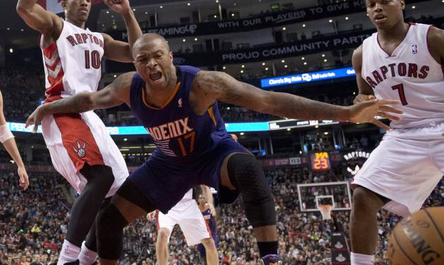 Phoenix Suns guard P.J.Tucker (17) lets out a yell after being fouled while rebounding against Toronto Raptors guards DeMar DeRozan (10) and Kyle Lowry (7) during the first half of an NBA basketball game in Toronto on Sunday, March 16, 2014. (AP Photo/The Canadian Press, Frank Gunn)