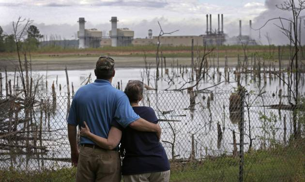 In this April 25, 2014 photo, Bryant Gobble, left, hugs his wife, Sherry Gobble, right, as they look from their yard across an ash pond full of dead trees toward Duke Energy's Buck Steam Station in Dukeville, N.C. Records obtained by The Associated Press show that Duke and North Carolina environmental regulators have known since 2011 that groundwater samples taken from monitoring wells near several homes in Dukeville contained substances, some that can be toxic, exceeding state standards. (AP Photo/Chuck Burton)