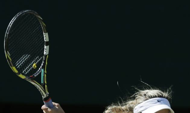 Eugenie Bouchard of Canada plays a return to Simona Halep of Romania during their women's singles semifinal match at the All England Lawn Tennis Championships in Wimbledon, London, Thursday, July 3, 2014. (AP Photo/Pavel Golovkin)