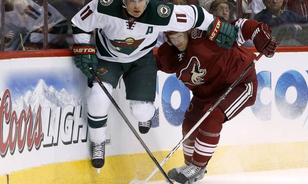 Minnesota Wild's Zach Parise (11) and Phoenix Coyotes' Zbynek Michalek, of the Czech Republic, collide behind the goal during the first period of an NHL hockey game, Saturday, March 29, 2014, in Glendale, Ariz. (AP Photo/Ross D. Franklin)
