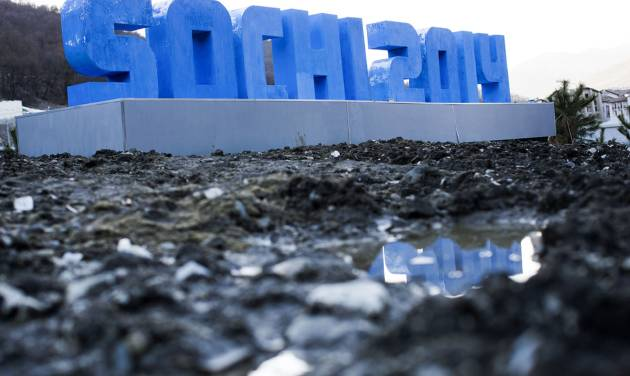 A Sochi 2014 logo of the 2014 Winter Olympics standing on mud and rubble in front of snow-covered mountains is reflected in a puddle, Monday, Feb. 3, 2014, in Krasnaya Polyana, Russia. (AP Photo/Gero Breloer)