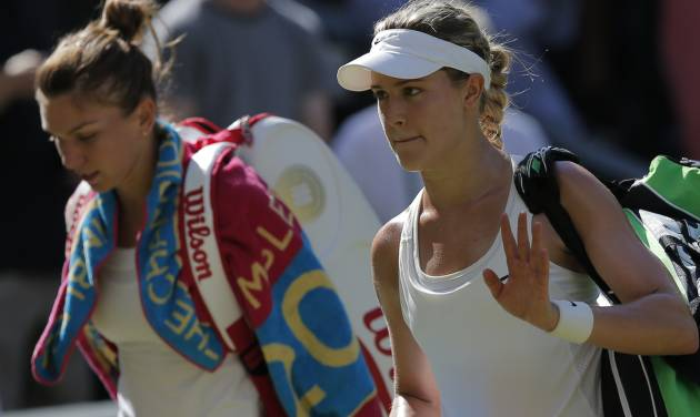 Eugenie Bouchard of Canada, right, waves as she walks off court with Simona Halep of Romania after she won their women's singles semifinal match at the All England Lawn Tennis Championships in Wimbledon, London, Thursday, July 3, 2014. Bouchard will play Petra Kvitova of Czech Republic in the final Saturday. (AP Photo/Pavel Golovkin)