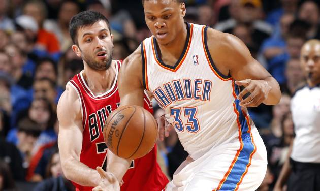 Oklahoma City's Daniel Orton (33) grabs a loose ball as Chicago's Vladimir Radmanovic (77) during the NBA game between the Oklahoma City Thunder and the Chicago Bulls at Chesapeake Energy Arena in Oklahoma City, Sunday, Feb. 24, 2013. Photo by Sarah Phipps, The Oklahoman