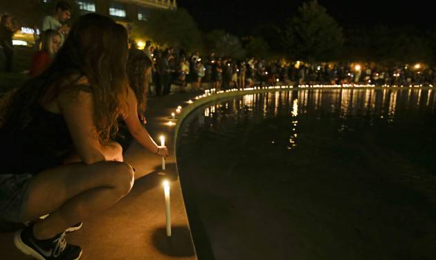 Students and supporters place candles at the edge of a wall surrounding a pond as they take part in a candle light vigil at the University of Central Florida, Wednesday, Sept. 3, 2014, in Orlando, Fla., to honor Steven Sotloff, the second American journalist to be beheaded by the Islamic State group in two weeks. Sotloff attended University of Central Florida between 2002 and 2004. (AP Photo/John Raoux)