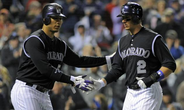 Colorado Rockies' Carlos Gonzalez (5) and Troy Tulowitzki (2) celebrate being driven in on a Todd Helton two-RBI single against the Arizona Diamondbacks during the fourth inning of a baseball game on Friday, April 13, 2012, in Denver. (AP Photo/Jack Dempsey)
