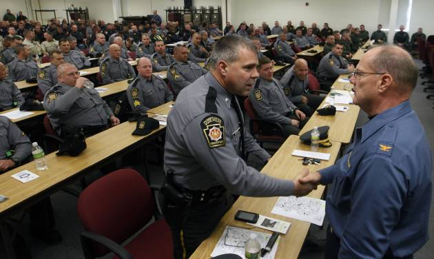 Pennsylvania Deputy State Police Commissioner Lt. Col.George Bivens, left, is greeted by New Jersey State Police Superintendent Colonel Rick Fuentes after 280 state troopers, police and law enforcement officers from other states were sworn in by New Jersey Attorney General Jeffrey S. Chiesa Monday, Nov. 5, 2012, at Joint Base McGuire-Dix-Lakehurst in Wrightstown, N.J. The officers will assist New Jersey state police and local officers with security and recovery missions in the wake of Superstorm Sandy. (AP Photo/Mel Evans)