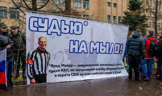 "In this handout photo provided by Young Guards of United Russia party press service shows a group of demonstrators holding a banner with a photo of American Ice Hockey referee Brad Meier and message reading "" Turn the referee into soap,"" which is indeed a Russian expression, as awful as it seems, as they protest against a controversial disallowed goal  Meier, who overturned Russia's third goal during the match between U.S. and Russia teams on Saturday near the U.S. Embassy in Moscow, Russia, Monday, Feb. 17, 2014. The demonstration was organized by the Young Guard, the youth wing of the Kremlin political party United Russia. (AP Photo/Voroshirin Dmitriy, Young Guards)"