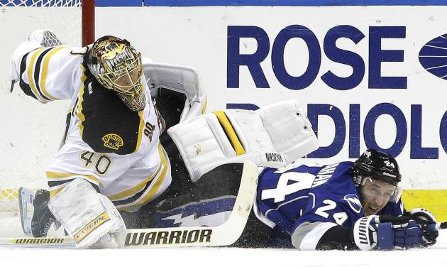 Tampa Bay Lightning right wing Ryan Callahan (24) takes down Boston Bruins goalie Tuukka Rask, of Finland, during the first period of an NHL hockey game on Saturday, March 8, 2014, in Tampa, Fla. Callahan was tripped and slid into Rask. (AP Photo/Chris O'Meara)