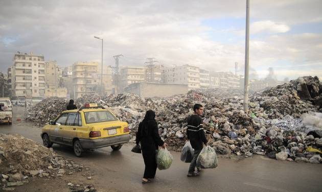 In this Saturday, Nov. 10, 2012 photo, Syrians carry their rubbish to a mountain of garbage in a roundabout in Aleppo, Syria. Due the heavy fighting and shelling, the garbage collection system collapsed weeks ago. (AP Photo/Mónica G. Prieto)