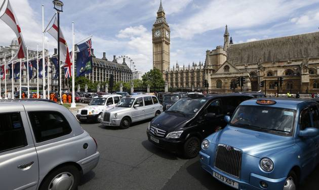 Taxi stand still at Parliament Square in central London as thousands of London black cabs blocking the streets to protest over new technology they say endangers passengers, in London, Wednesday, June 11, 2014.  The strike action by taxi drivers hit many European cities, Wednesday, sparked by fears about the growing upheaval in the travel and transport industry, largely due to digital technologies. Big Ben's clock tower back centre. (AP Photo/Sang Tan)