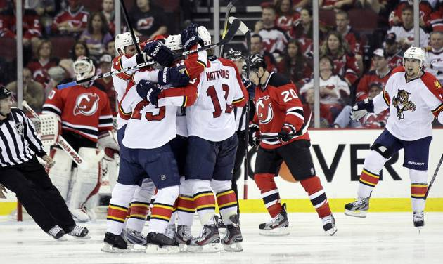 The Florida Panthers celebrate a goal by Mike Weaver during the second period of Game 3 of a first-round NHL hockey Stanley Cup playoff series against the New Jersey Devils, Tuesday, April 17, 2012, in Newark, N.J. (AP Photo/Julio Cortez)