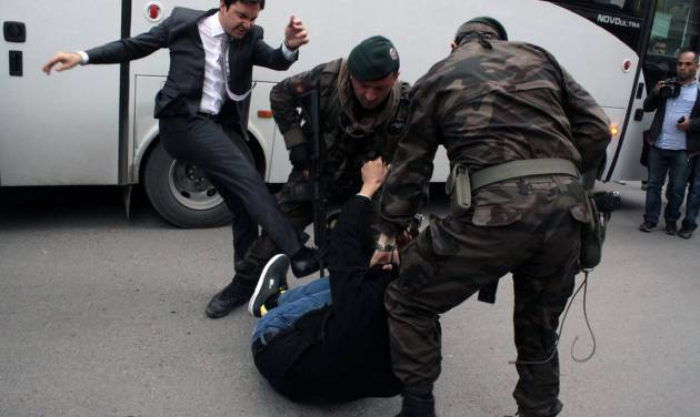 In this photo taken Wednesday, May 14, 2014  a person identified by Turkish media as Yusuf Yerkel, advisor to Turkish Prime Minister Recep Tayyip Erdogan, kicks a protester already held by special forces police members during Erdogan's visiting  Soma, Turkey. Erdogan was visiting the western Turkish mining town of Soma after Turkey's worst mining accident . AP Photo/Depo Photos) TURKEY OUT