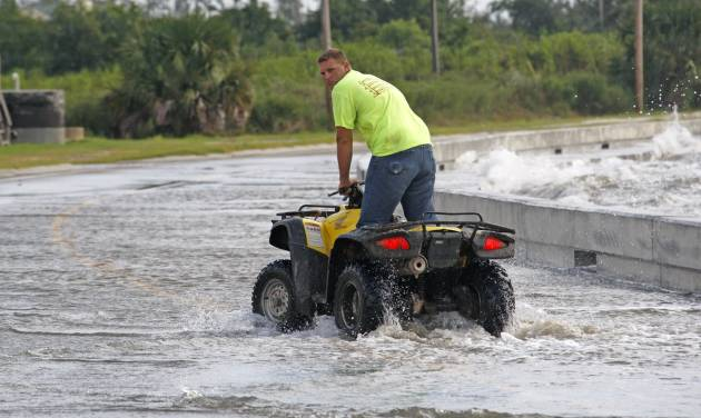 Brandon Ellis of Waveland takes advantage of the height of his ATV to ride up to the waves coming over the seawall alongside Beach Boulevard in Waveland, Miss., as Isaac's winds begin to hit the Mississippi Gulf Coast, Tuesday, Aug. 28, 2012. (AP Photo/Rogelio V. Solis)