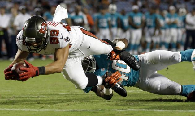 Tampa Bay Buccaneers wide receiver David Douglas (89) stretches for a touchdown as Miami Dolphins defensive back Keelan Johnson (40) holds his legs during the second half of an NFL preseason football game on Saturday, Aug. 24, 2013, in Miami Gardens, Fla. The Buccaneers defeated the Dolphins 17-16. (AP Photo/Lynne Sladky)