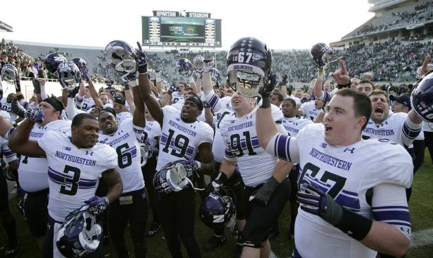 Northwestern players celebrate their 23-20 win over Michigan State in an NCAA college football game, Saturday, Nov. 17, 2012, in East Lansing, Mich. (AP Photo/Al Goldis)
