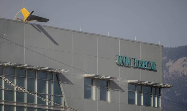 A helicopter's tail hangs over the edge of the UNM Hospital  Wednesday afternoon, April 9, 2014, when it crashed as it took off from the roof of the building.    (AP Photo/The Albuquerque Journal, Roberto E. Rosales)  THE SANTA FE NEW MEXICAN OUT
