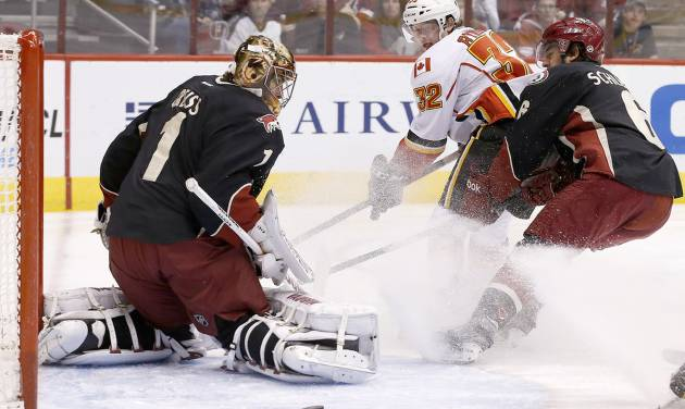 Phoenix Coyotes' Thomas Greiss (1), of Germany, makes a save on a shot by Calgary Flames' Paul Byron (32) as Coyotes' David Schlemko, right, defends during the first period of an NHL hockey game, Tuesday, Jan. 7, 2014, in Glendale, Ariz. (AP Photo/Ross D. Franklin)