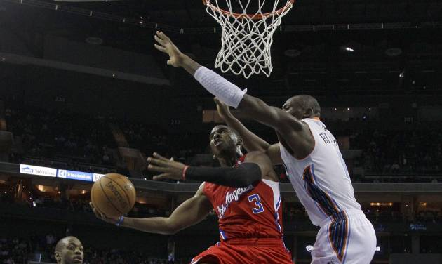 Los Angeles Clippers' Chris Paul, center, shoots as Charlotte Bobcats' Bismack Biyombo, right, and Kemba Walker, left, defend during the first half of an NBA basketball game in Charlotte, N.C., Wednesday, Dec. 12, 2012. (AP Photo/Chuck Burton)