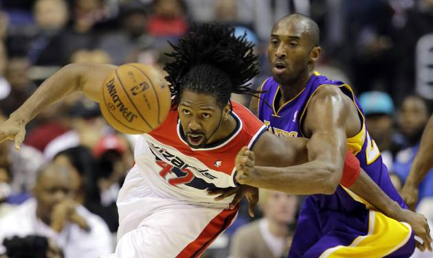 Washington Wizards center Nene, from Brazil, and Los Angeles Lakers guard Kobe Bryant go for the loose ball in the first half of an NBA basketball game Friday, Dec. 14, 2012 in Washington. (AP Photo/Alex Brandon)