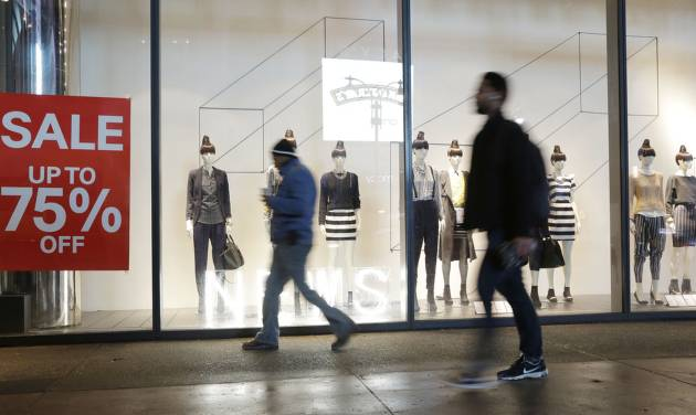 FILE - In this Jan. 14, 2014 file photo, pedestrians pass an H&M storefront window advertising discounts up to 75%, in New York. The Commerce Department reports how much consumers spent and earned in January on Monday, March 3, 2014. (AP Photo/Mark Lennihan, File)