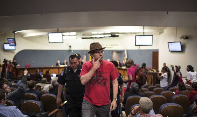 Activist David Correia motions to Albuquerque Police chief Gorden Eden as Correia is escorted from city council chambers in Albuquerque, N.M., Thursday, May 8, 2014. At least seven people were removed from the chambers and given a criminal trespass notice saying not to return to council chambers for 90 days. The Albuquerque City Council gathered Thursday under new rules and heightened security designed to avoid an angry confrontation like the one that broke out earlier in the week amid community outrage over a spate of deadly police shootings. (AP Photo/Juan Antonio Labreche)