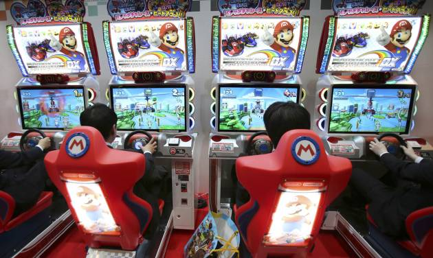 FILE - In this Feb. 15, 2013 file photo, visitors try out the Mario Kart Arcade GP DX racing game exhibited by Namco Bandai and Nintendo on the business day of the Japan Amusement Expo in Makuhari, near Tokyo. Nintendo Co. reported Wednesday, April 24, the Kyoto-based maker of Super Mario and Pokemon games returned to profit for the fiscal year ended March 31 as a lift from the weak yen offset sales struggles caused by software delays for its latest home console Wii U. (AP Photo/Koji Sasahara, File)