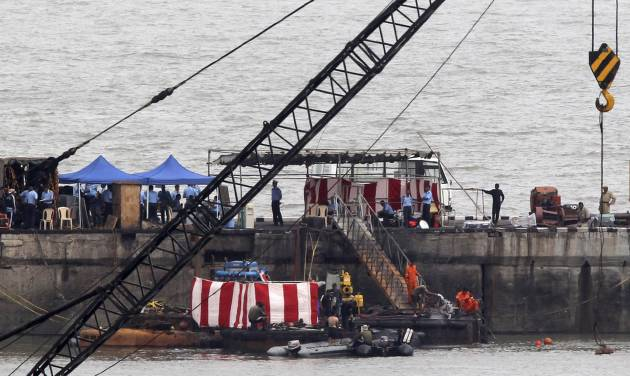 Navy divers stand around the 16-year-old diesel-powered, Russian-made submarine INS Sindhurakshak, covered with a red and white sheet, at the Naval Dockyard in Mumbai, India, Friday, Aug. 16, 2013. Indian navy divers on Friday recovered four severely burned bodies of sailors who had been trapped inside the submarine damaged by twin explosions, officials said. The navy said it was doubtful that any of the other 14 sailors aboard survived. (AP Photo/Rajanish Kakade)