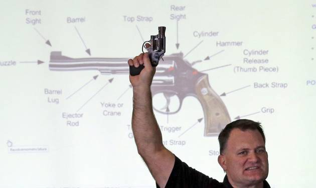 "FILE - In this Dec. 27, 2012, file photo, Clark Aposhian, president of Utah Shooting Sport Council, holds a pistol during concealed weapons training for 200 Utah teachers, in West Valley City, Utah, with a diagram of gun parts projected behind him. Utah's top gun lobbyist will once again be able to access his arsenal after resolving a criminal case against him. On Monday, June 23, 2014, Aposhian pleaded no contest to a disorderly conduct infraction stemming from honking a horn, and was ordered to pay a $320 fine. His lawyer says Aposhian feels ""vindicated"" that other counts, including a domestic violence charge, were dismissed. (AP Photo/Rick Bowmer, File)"