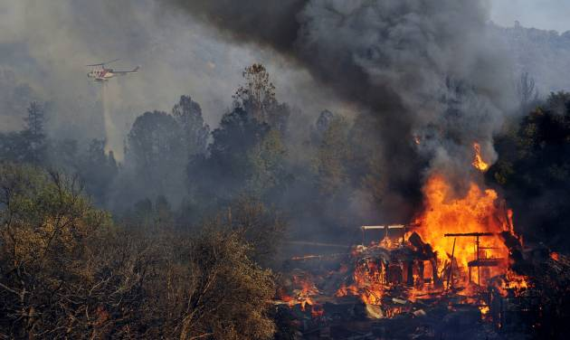 A structure burns along Highway 41 in Oakhurst, Calif., Monday, Aug. 18, 2014. One of several wildfires burning across California prompted the evacuation of hundreds of people in a central California foothill community near Yosemite National Park, authorities said. (AP Photo/The Fresno Bee, Eric Paul Zamora)