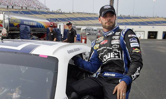 Jimmie Johnson steps from his car after securing the pole position for Saturday's NASCAR Sprint Cup Series auto race at Kentucky Speedway in Sparta, Ky., Friday, June 29, 2012. (AP Photo/James Crisp)