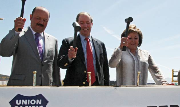 State of Chihuahua, Mexico, Governor Cesar Duarte, left, U.S. Sen. Tom Udall, center, and New Mexico Governor Susana Martinez hammer golden spikes during a railroad hub opening ceremony in Santa Teresa, New Mexico, Wednesday, May 28, 2014. A sprawling $400 million railroad hub opened in this border town and it is expected to create up to 600 jobs and attract businesses. (AP Photo/Juan Carlos Llorca)