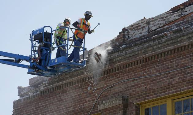 Contractors pull loose bricks from the roof of an earthquake damaged 36,000 square foot former boat shop on Mare Island Tuesday, Aug. 26, 2014, in Vallejo, Calif. The building dates from 1904 and was used by the Navy. The bayside city that twice was briefly the capital of California sustained more than $5 million in damage and dozens of injuries. It was the latest blow to a town that has weathered years of bankruptcy and is now beset by gangs and crime. (AP Photo/Eric Risberg)
