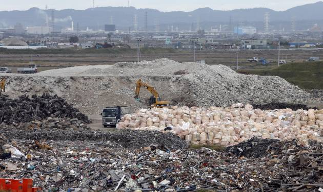 In this Oct. 10, 2012 photo, a yellow crane sorts out the rubble of the March 11, 2011 earthquake and tsunami, at the rubble collection site near the Arahama beach in Sendai, northeastern Japan. Japan's accounting of its budget for reconstruction from the disasters is crammed with spending on unrelated projects, while all along Japan's northeastern coast, dozens of communities remain uncertain of whether, when and how they will rebuild. (AP Photo/Koji Sasahara)