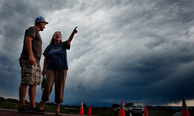 Jasen Dill, left, and Judy Pohlod discuss returning to their homes, which made it through the Black Forest fire safely, as a storm passes overhead at the corner of Hodgen Road and Highway 83 Friday, June 14, 2013 in Colorado Springs, Colo. . (AP Photo/The Colorado Springs Gazette, Michael Ciaglo) MAGS OUT
