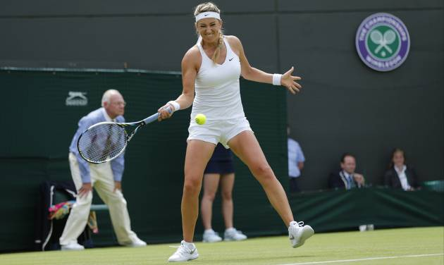 Victoria Azarenka of Belarus returns against Mirjana Lucic-Baroni of Croatia during their first round match at the All England Lawn Tennis Championships in Wimbledon, London, Monday, June 23, 2014. (AP Photo/Ben Curtis)