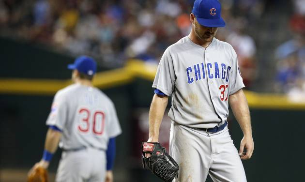 Chicago Cubs' Travis Wood, right, pauses at the pitcher's mound after getting a visit from teammates, including Mike Olt (30), as Wood gives up four runs during the fifth inning of a baseball game against the Arizona Diamondbacks on Saturday, July 19, 2014, in Phoenix. (AP Photo/Ross D. Franklin)