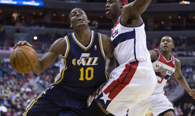 Washington Wizards  forward Al Harrington stops a drive by Utah Jazz point guard Alec Burks (10) during the second half of an NBA basketball game on Wednesday, March 5, 2014, in Washington. The Wizards defeated the Jazz 104-91. At right is Washington Wizards shooting guard Bradley Beal. (AP Photo/ Evan Vucci)